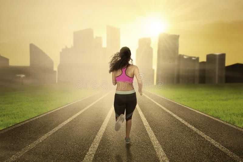 Fitness woman running at field toward city stock photos