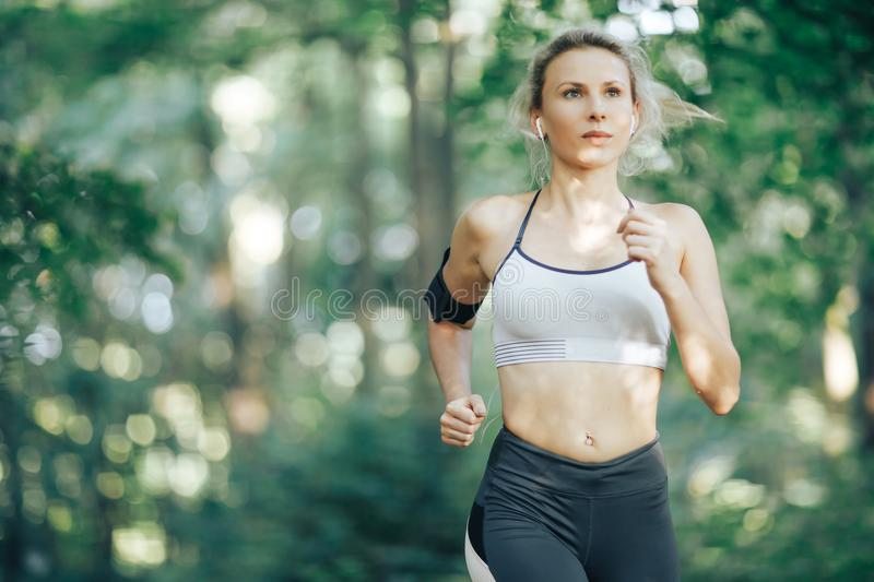 Fitness woman running in the morning park stock images