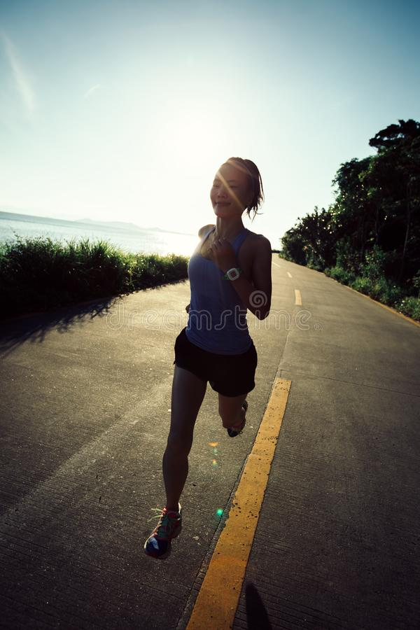 Woman running on seaside trail royalty free stock photography