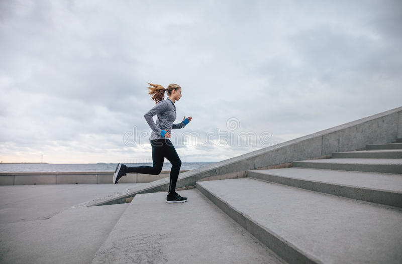 Fitness woman running up on steps royalty free stock photo