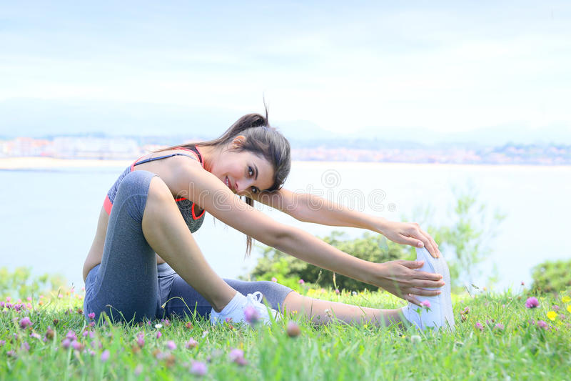 Fitness woman by the seaside stretching royalty free stock photography