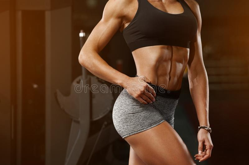 Fitness woman showing abs and flat belly in gym. Athletic girl, shaped abdominal, slim waist stock image