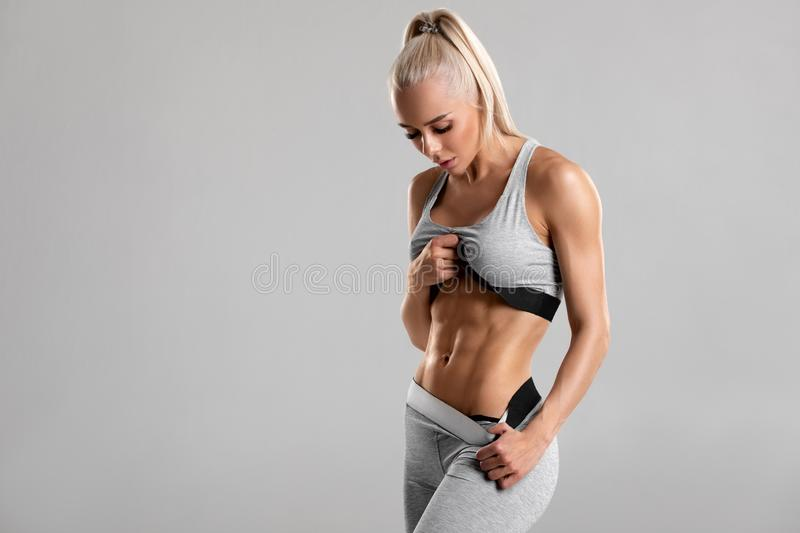 Fitness woman showing abs and flat belly, isolated on gray background. Beautiful athletic girl, shaped abdominal.  royalty free stock photos