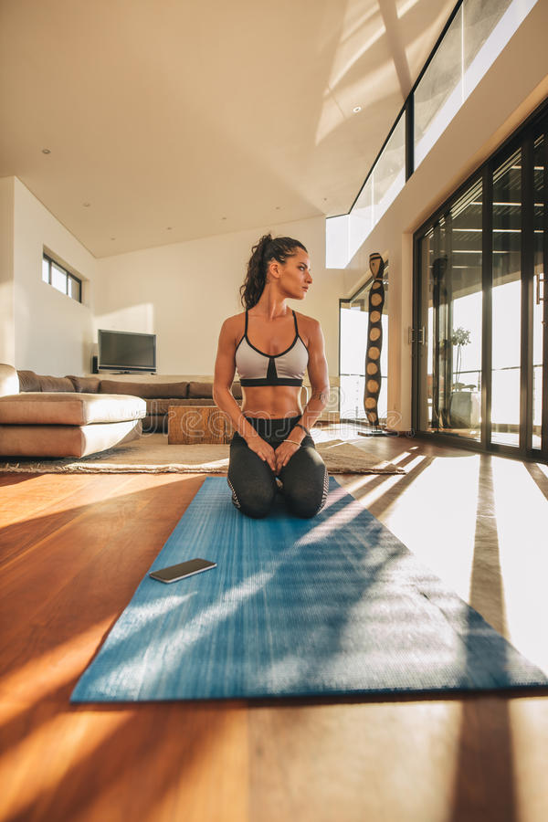 Fitness woman sitting Vajrasana yoga pose. Shot of fitness woman sitting Vajrasana yoga pose and looking away. Fit young woman practicing yoga at home stock photo