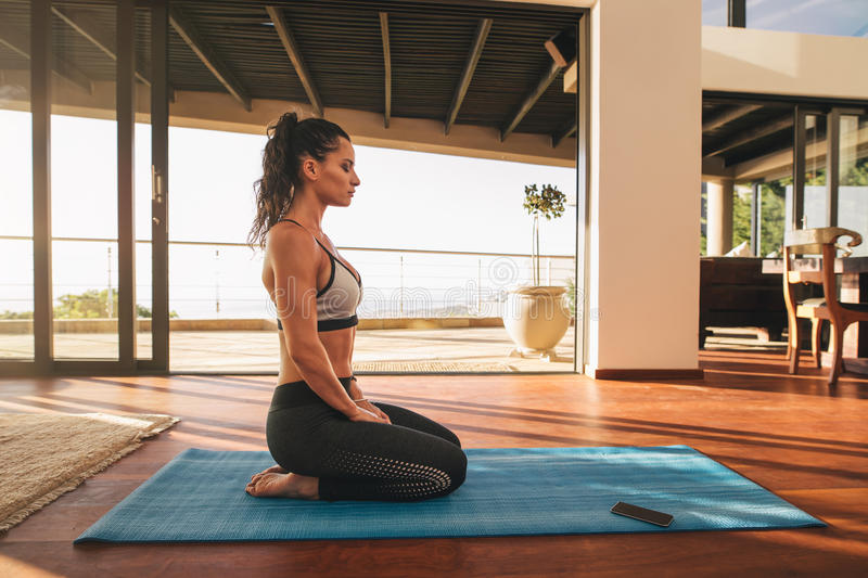 Fitness woman sitting in yoga pose at home. Side view shot of fitness woman sitting in yoga pose at home. Female in sportswear doing meditation on exercise mat stock photography