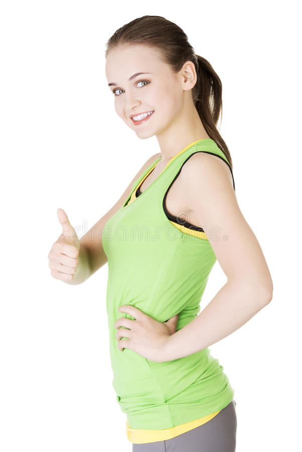 Fitness woman in sport clothes gesturing thumbs up. Attractive fitness woman in sport clothes gesturing thumbs up, isolated on white stock photography