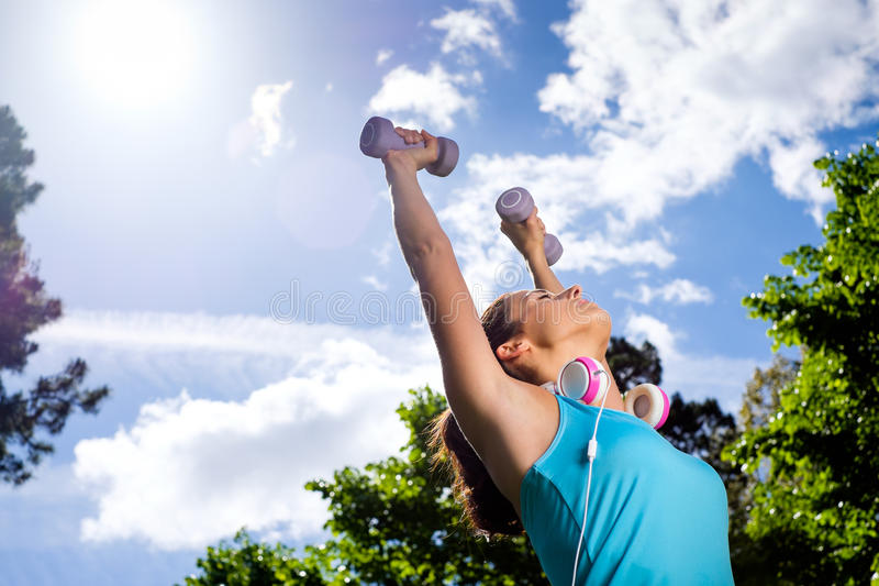 Fitness woman in sport lifestyle working out. Fitness woman working out with dumbbells in city park. Spring or summer exercising workout with weights. Urban royalty free stock photo