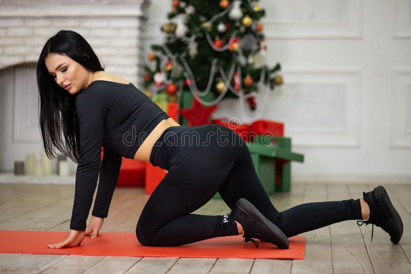 Fitness woman in sport style with Christmas tree on background. Merry Christmas and Happy New Year. Fitness woman in sport style clothes with Christmas tree on stock photos
