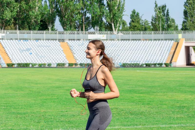 Fitness woman in sportswear listening music and running at the football stadium. Sports and healthy concept royalty free stock photo