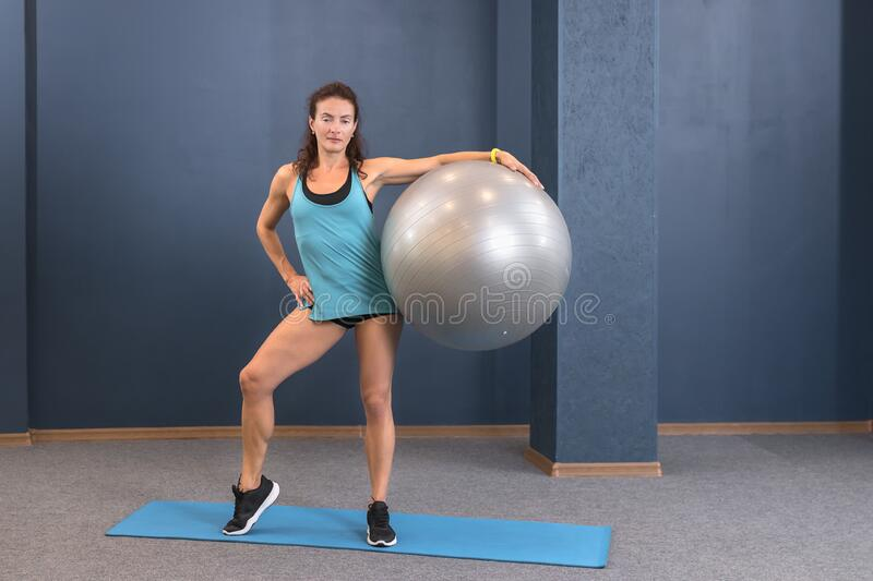 Fitness woman in sportswear staying on yoga mat at gym and posing with fit ball. Concept of sport health life with copy space stock photo