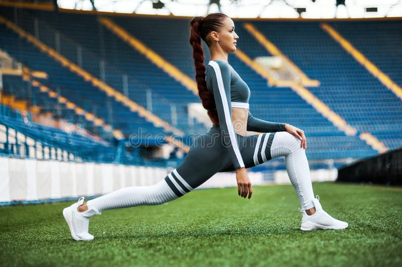 Fitness woman on stadium. Healthy sports lifestyle. Athletic young female in sports wear doing fitness exercise stock photography