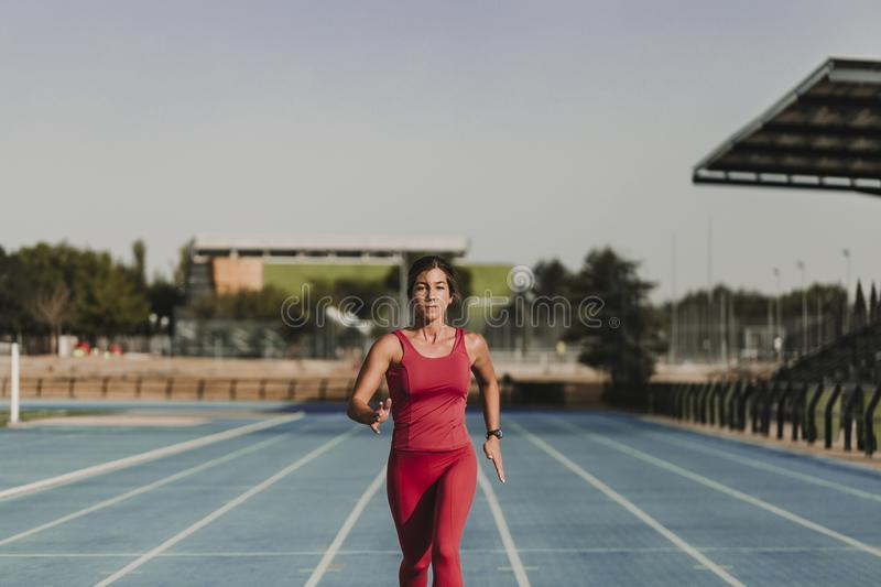 Fitness woman on stadium running by blue tracks. Wearing Red sport clothes. healthy lifestyle concept. Sunset at summer royalty free stock image