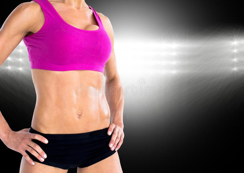 Fitness woman standing with hands on her hip against black background royalty free stock photography