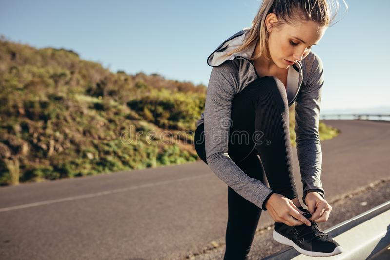 Fitness woman standing on roadside tying her shoelace. Woman in fitness wear tightening her shoelace on the side railing of the stock photo
