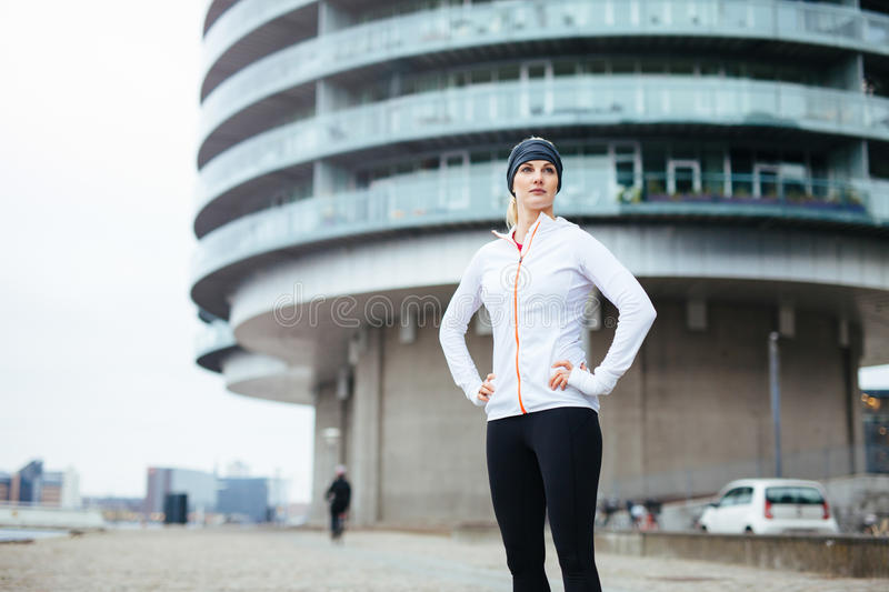 Fitness woman standing on street. Portrait of a beautiful young woman standing on urban street while out for a run in the city. Fitness female standing with her royalty free stock photography