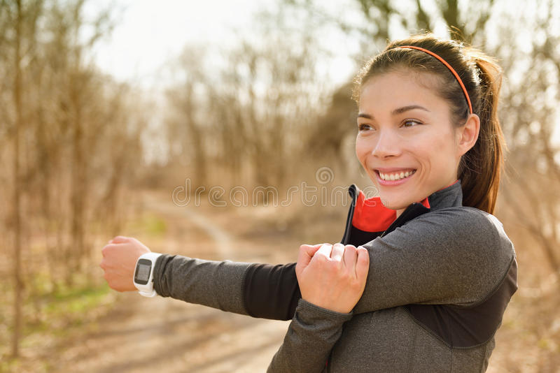 Fitness woman stretching arms with smartwatch. Before running or cardio workout. Happy Asian girl doing warm-up before jogging with heart rate monitor in stock photos