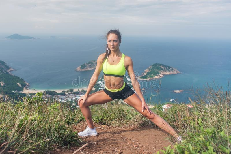 Fitness woman stretching her leg muscles doing side lunge exercise preparing for cardio work-out in mountains by the sea stock photos