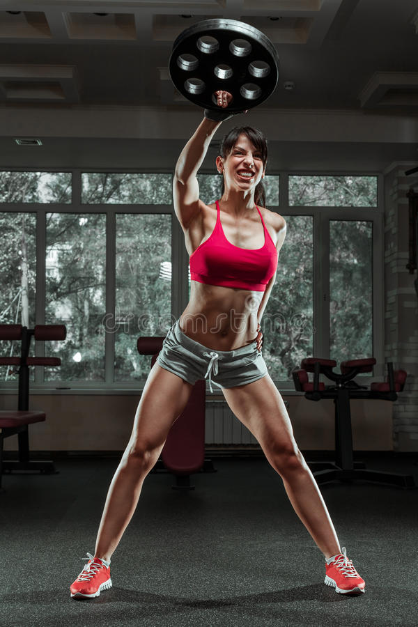 Fitness woman swinging kettle bell at gym. Young caucasian woman doing swing exercise with a kettlebell as a routine of a crossfit workout royalty free stock photo