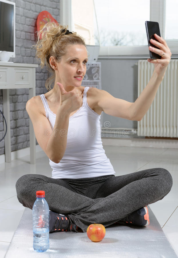 Fitness woman taking photo with her smartphone, after exercisin. Young fitness woman taking photo with her smartphone, after exercising stock image