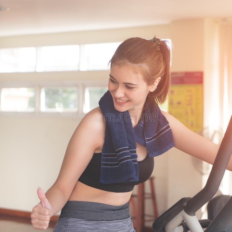 Fitness woman with thumb up for success on working out in fitness gym stock photos