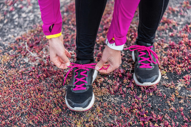 Fitness woman trail runner lacing running shoes stock images