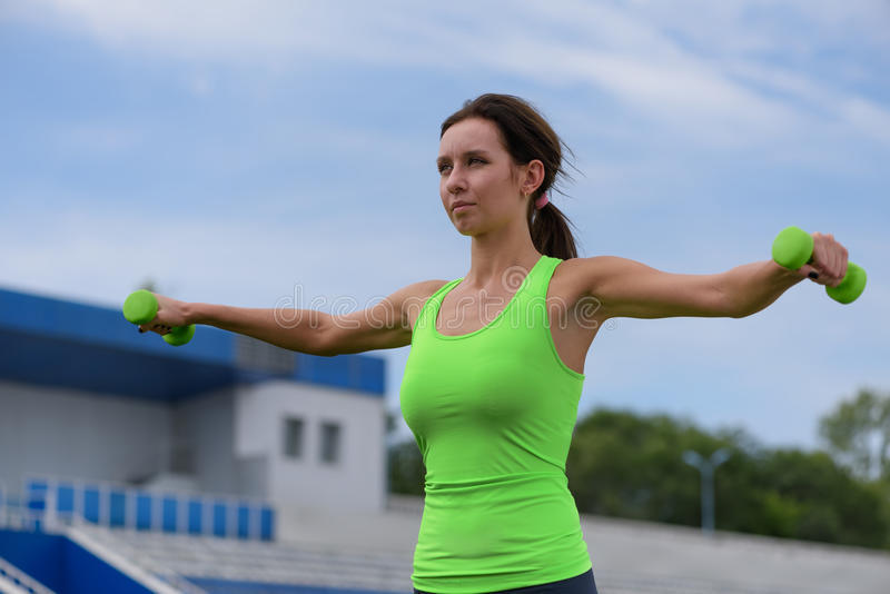 Fitness woman training with dumbbell at the stock photos