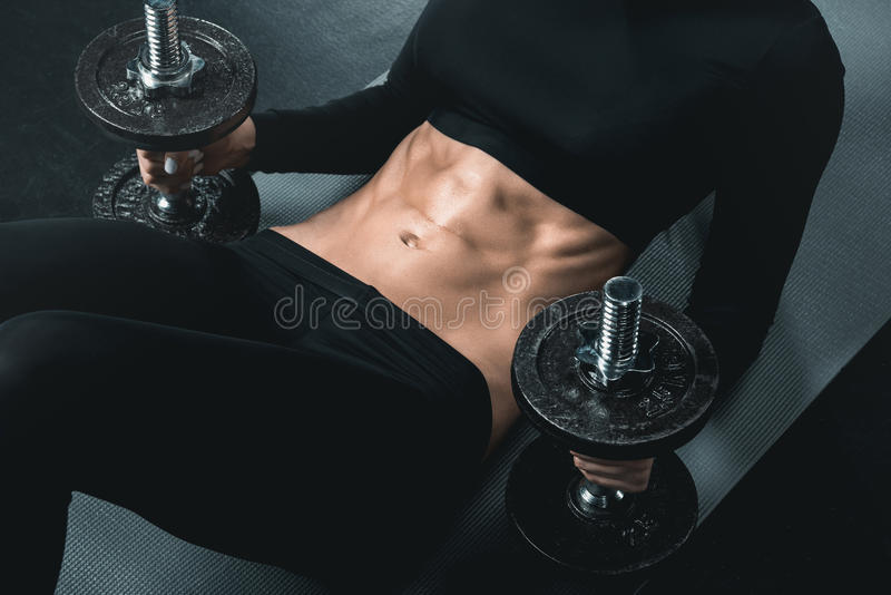 Fitness woman training with dumbbells and doing abs on mat. royalty free stock photo