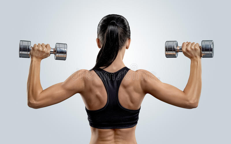 Fitness woman in training muscles of the back with dumbbells royalty free stock photos