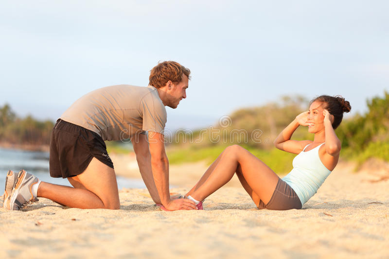 Fitness woman training situp crunches with trainer. Fitness women training situp crunches with personal trainer instructor. Young couple happy working out in stock photo