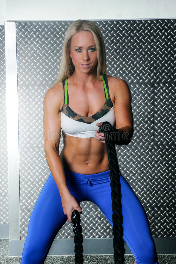 Fitness woman using battling ropes stock images
