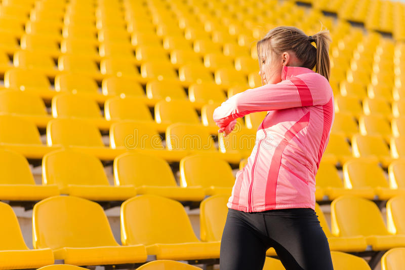 Fitness woman warming up at stadium stock photo