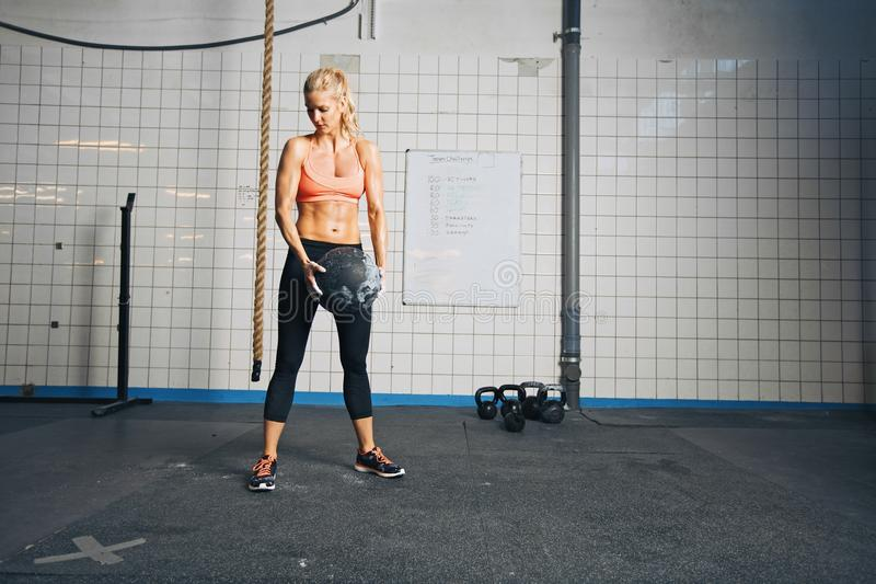 Fitness woman working out with a medicine ball. Strong young caucasian woman doing crossfit workout at gym stock photo