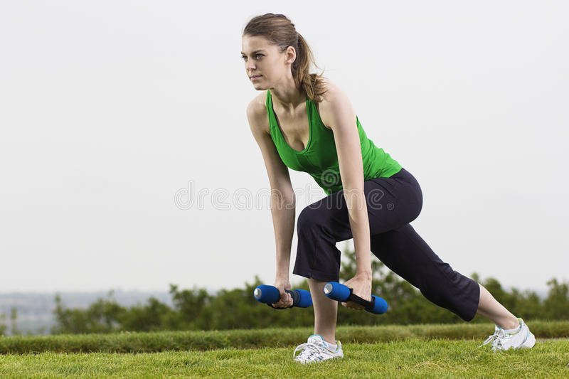 Fitness woman working out outdoors. A beautiful young fitness woman doing weight training outdoors. lots of copy space royalty free stock photos