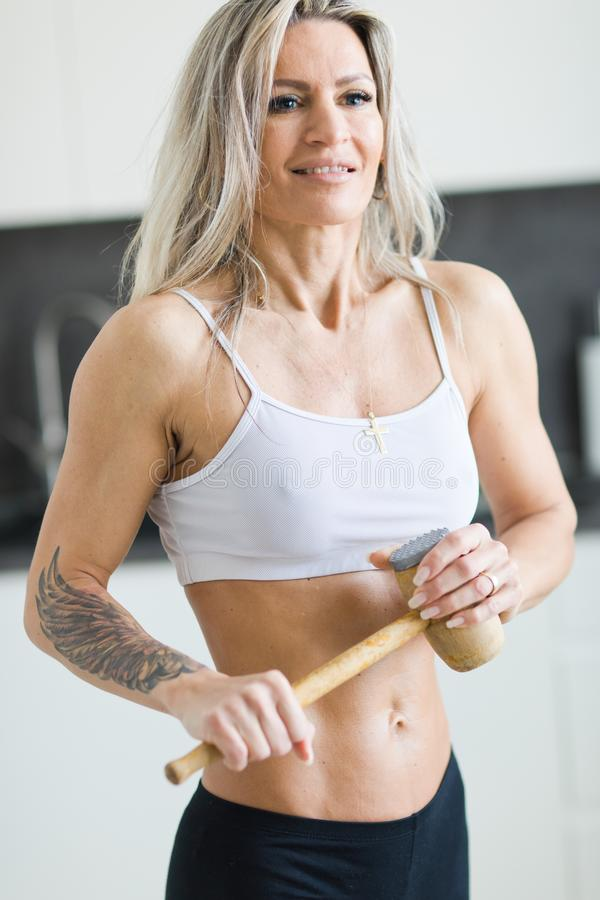 Fitness woman with workout body in kitchen posing with meat mallet stock images