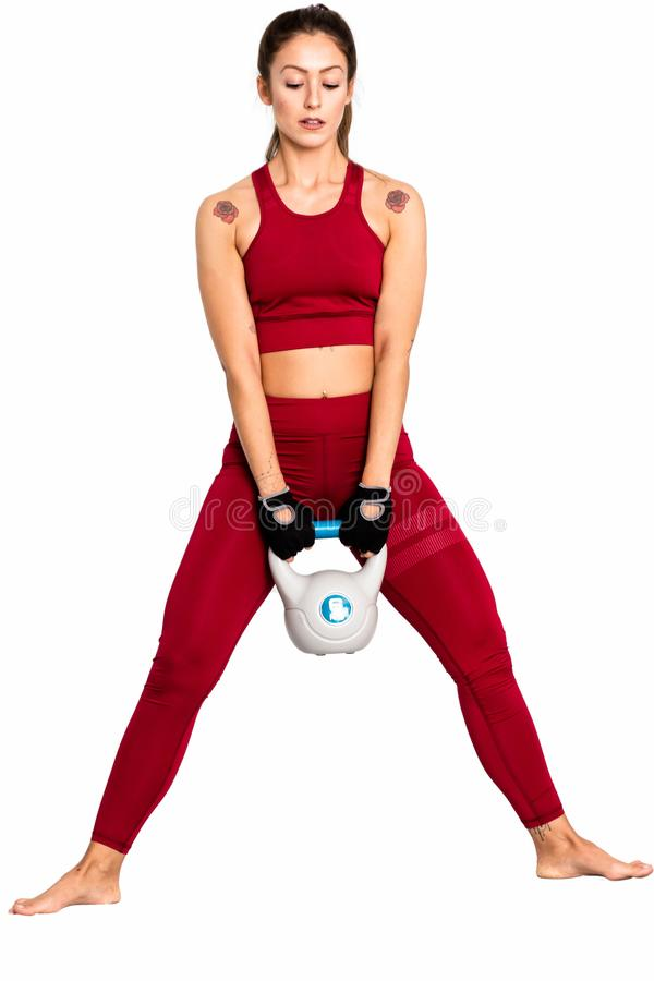 Fitness woman workout with kettlebell. Photo of  woman isolated on white background. Strength  - Image. Sporty woman doing squats with kettlebell. Photo of stock image