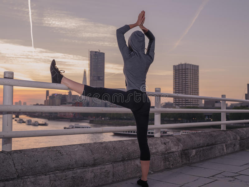 Fitness woman in yoga pose on bridge at sunrise. A young fitness woman is standing in a yoga pose on a bridge in London at sunrise royalty free stock photography