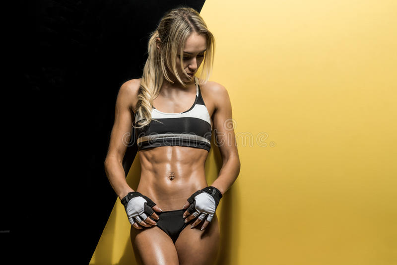 Fitness woman. Young fitness woman on black and yellow background, horizontal photo stock photo
