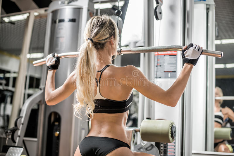 Fitness woman. Young fitness woman execute exercise with exercise-machine in gym, horizontal photo stock photos