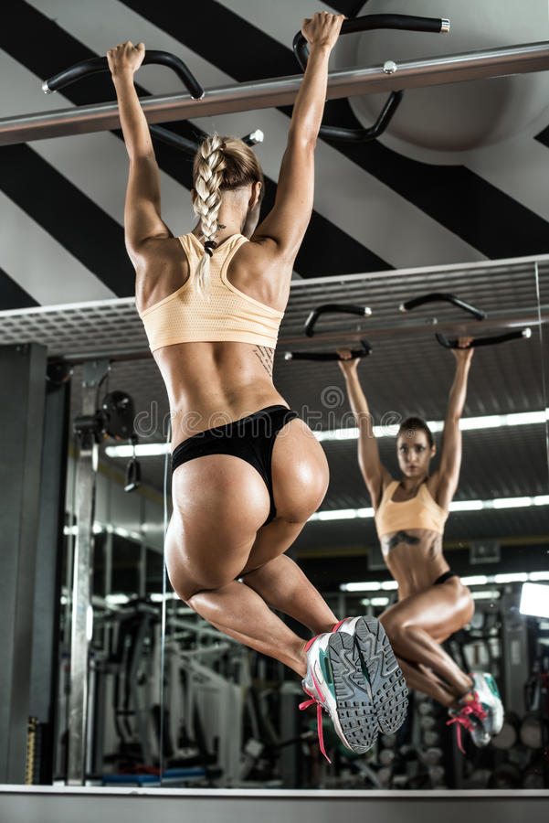 Fitness woman. Young fitness woman execute exercise on prelum abdominale, on horizontal bar in gym, vertical photo royalty free stock photos