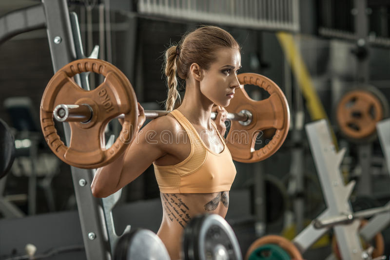 Fitness woman. Young fitness woman execute exercise with weight in gym, horizontal photo stock images