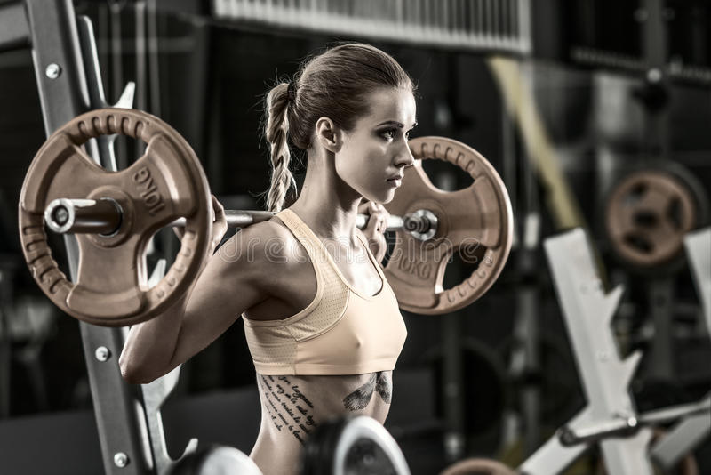 Fitness woman. Young fitness woman execute exercise with weight in gym, horizontal photo stock photography
