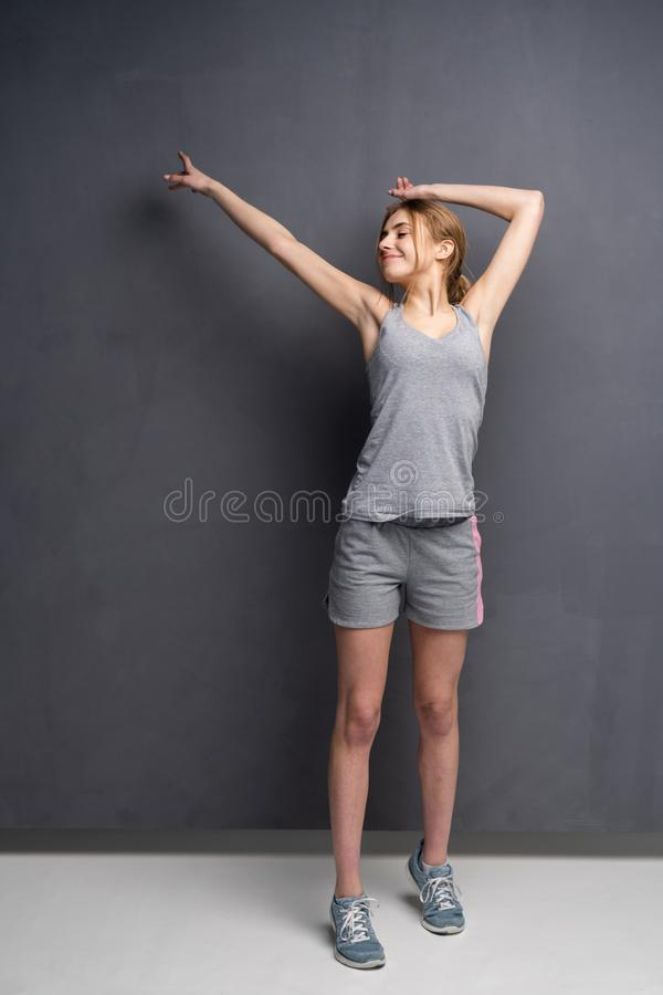 Fitness woman. Young sporty Caucasian female model isolated on gray background in full body. Fitness woman. Young sporty Caucasian female model isolated on gray royalty free stock images