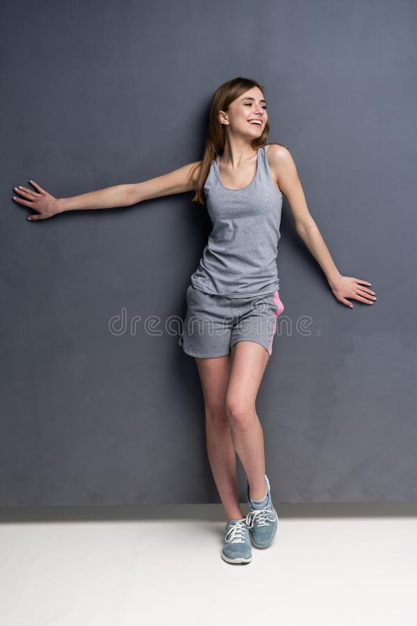 Fitness woman. Young sporty Caucasian female model isolated on gray background in full body. Fitness woman. Young sporty Caucasian female model isolated on gray stock image