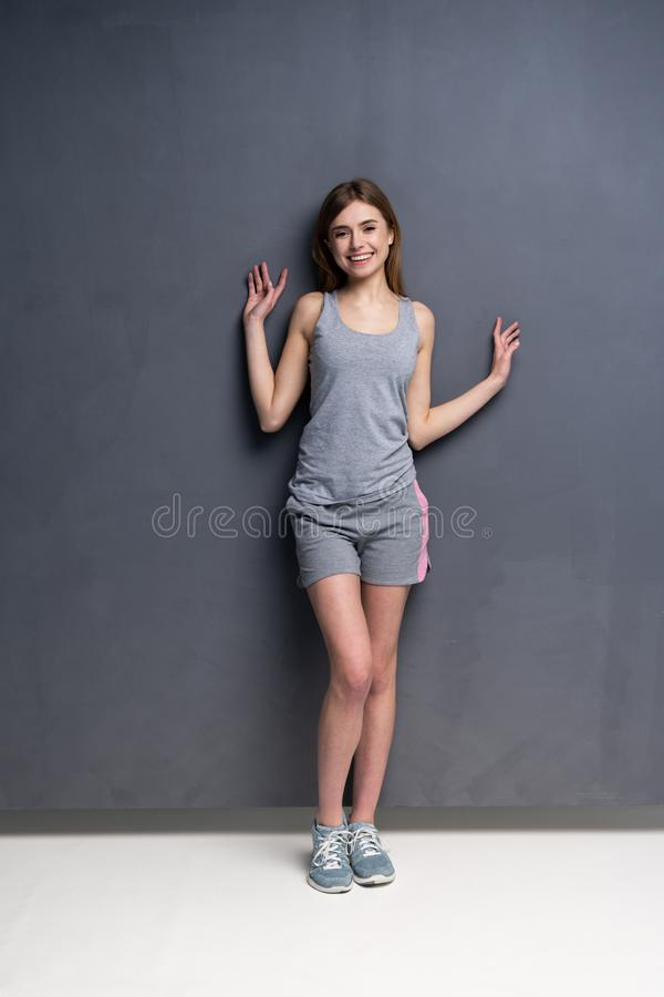 Fitness woman. Young sporty Caucasian female model isolated on gray background in full body. Fitness woman. Young sporty Caucasian female model isolated on gray royalty free stock image