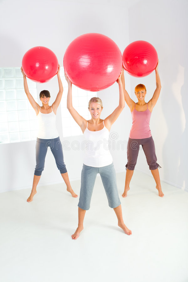 Fitness women. Group of women doing fitness exercise with big ball. They're looking at camera. Front view royalty free stock image