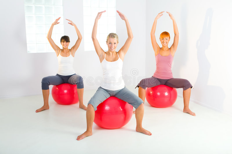 Fitness women. Group of women doing fitness exercise. They sitting on big balls with hands raised up. They're looking at camera. Front view royalty free stock images