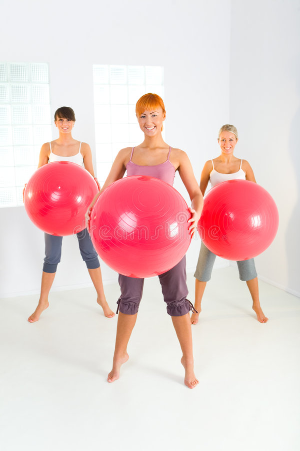 Fitness women. Group of women doing fitness exercise with big ball. They're looking at camera. Front view stock photo