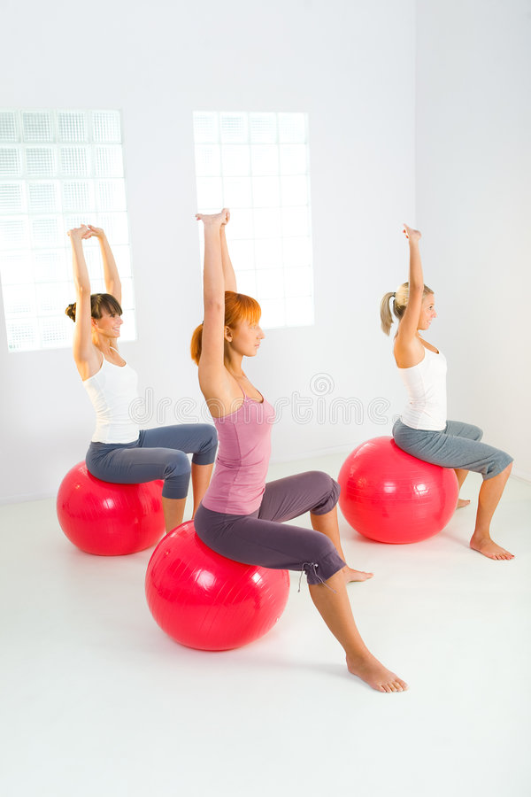 Fitness women. Group of women doing fitness exercise. They sitting on big balls with hands raised up. They're looking at camera. Side view royalty free stock image