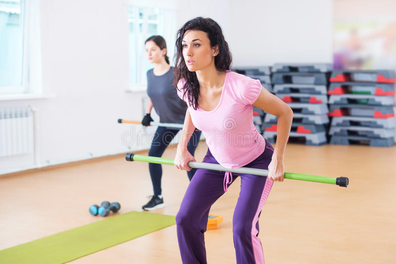 Fitness women warming up, exercising doing workout in fitness club royalty free stock photo