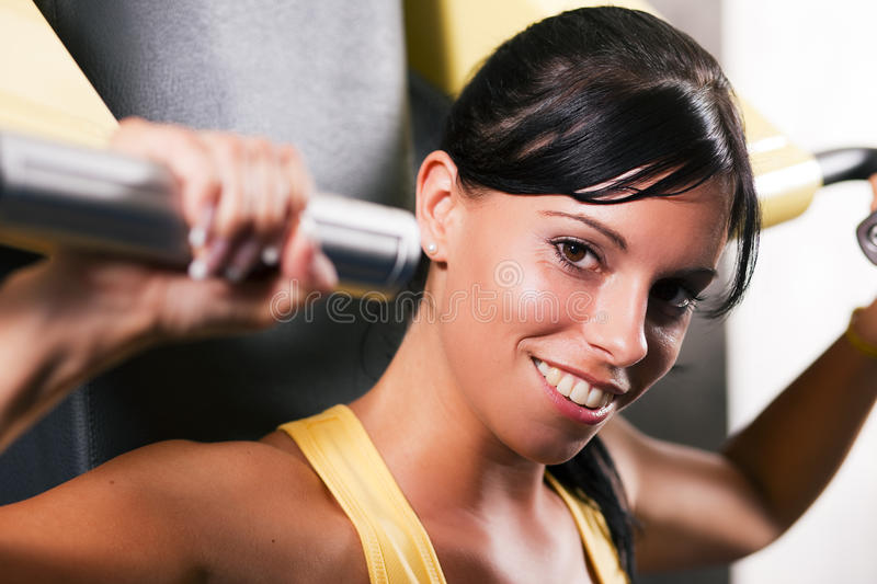 Fitness workout in gym. Very fit and beautiful young woman in a gym working out and lifting weights on an exercising machine royalty free stock photo
